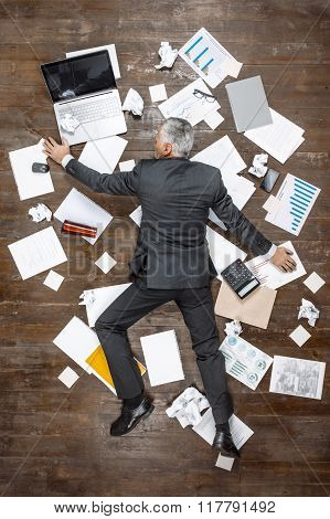 Top view creative photo of senior businessman on vintage brown wooden floor. Businessman sleeping on office objects. There are documents on floor