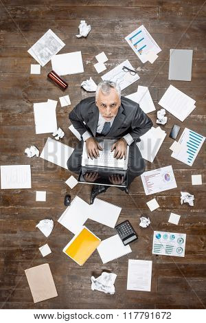 Top view creative photo of senior businessman on vintage brown wooden floor. Businessman sitting on office objects, looking at camera and working with laptop. There are documents on floor