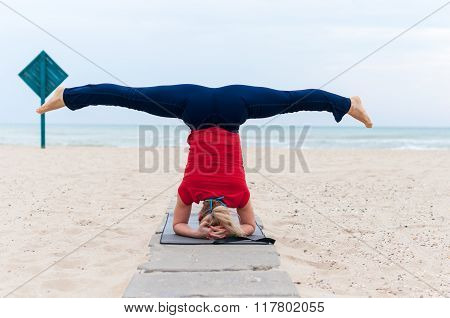 Woman doing yoga asana upavishtha konasana shirshasana, Bound Angle Pose in Head Stand on sea backgr