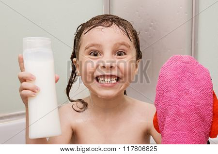 Little smiling girl in the shower with a washcloth and shampoo in her hands