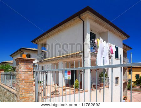 Fence Of White Two-story Cottage With Garden And Balcony With Hanging Clothes