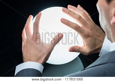 Businessman Predicting Future On Crystal Ball