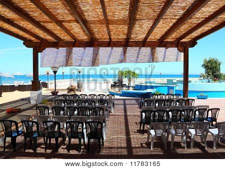 Chair Rows On The Balcony With Thatched Roof Overlooking Sea View At Sunny Day