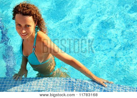 Smiling Girl In Blue Bikini With Brown Curly Hair Stands In Swimming-pool