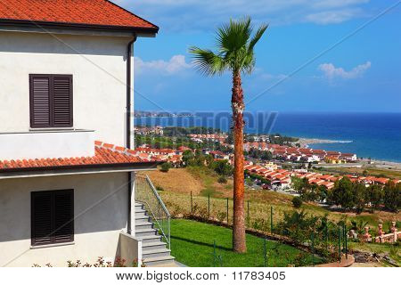 Big White Two-story House With Brown Roof, Palm Trees And Stairs On Coast At City