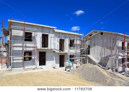 Building Of New Two-story White Concrete House With Stairs And Balcony