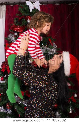 Mother Raise Child In Front Of Xmas Tree