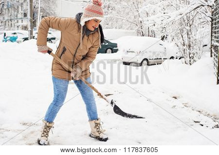 Woman Shoveling Snow In Parking