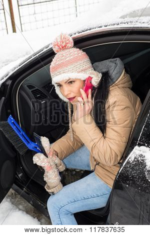 Woman Having Trouble With Car In Snow