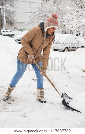 Woman Cleaning Snow  In Parking