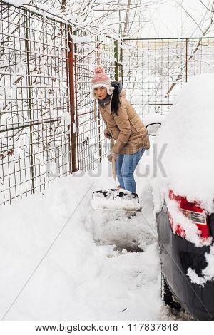 Woman Shoveling Snow Around Car