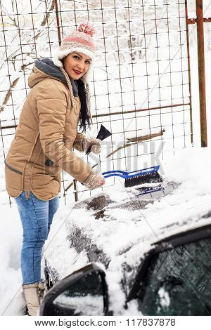 Woman Removing Snow On Car