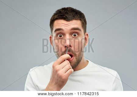beauty and people concept - smiling young man with tweezers tweezing hair frome nose over gray background