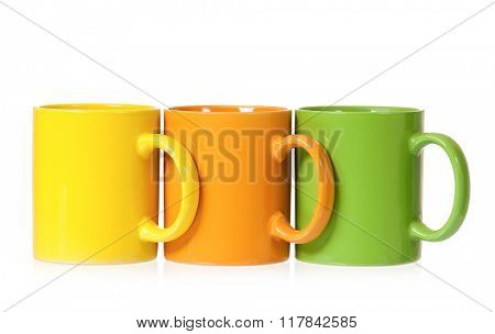 Three colorful mugs for coffee or tea, isolated on white background