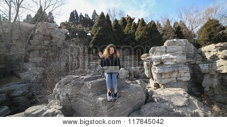 Beautiful young girl sitting with a laptop in the park on a background of mountains. The possibilities are endless on the Internet to work, learn, communicate. Speak with family online.