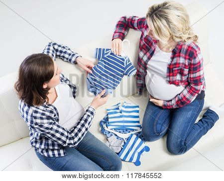 Two expectant mothers checking out children's wear.