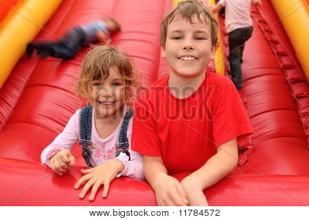 Little Boy And Girl Lying On Red Inflatable Slide, Smiling And Looking At Camera