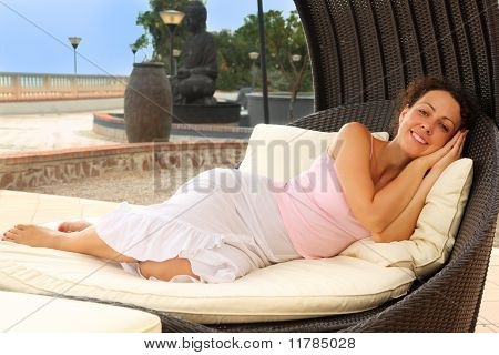 Beautiful Young Woman Lying On White Cushions In Black Wicker Chair, Statue, Trees And Lanterns