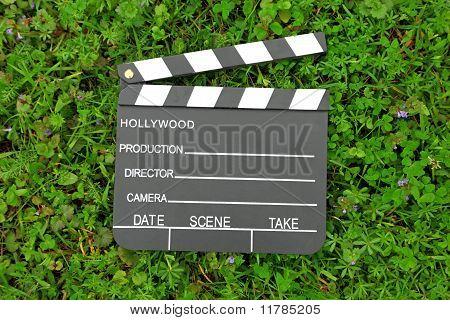 Cinema clapper board on green grass among flowering small purple flowers