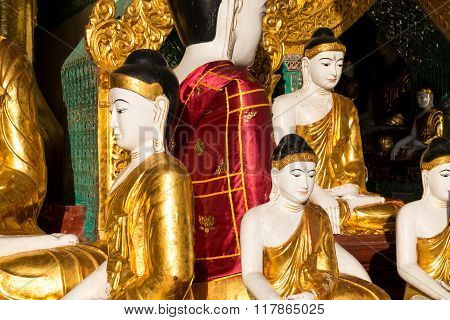 Close Up Of Different Sized Golden Buddhas, One With A Silky Red Cloak At The Shwedagon Pagoda