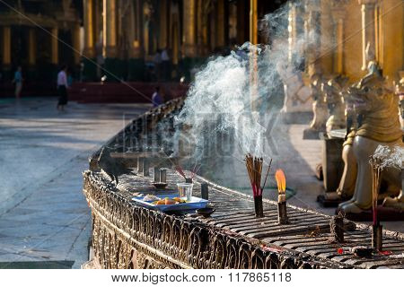 Incense Burns With A Try Of Offerings At The Shwedagon Pagoda In The Early Morning Sun