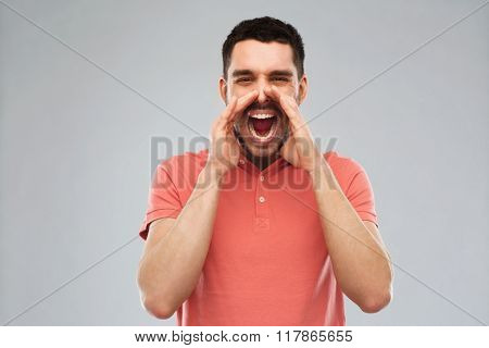 emotions, communication and people concept - angry shouting man in t-shirt over gray background