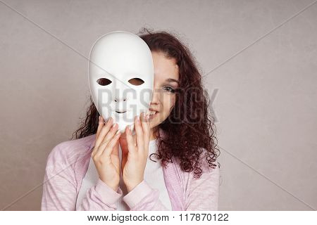 happy girl peeking behind mask