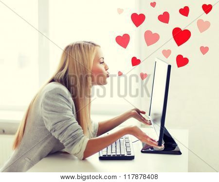 virtual relationships, online dating and social networking concept - woman sending kisses with computer monitor