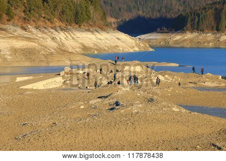 BAVARIA, GERMANY - DECEMBER, 2015 : People exploring the ruin of sunken old village Fall at Sylvenstein Reservoir dam in Bavaria, Germany on December 30, 2015. Village resurfaced during the renovation