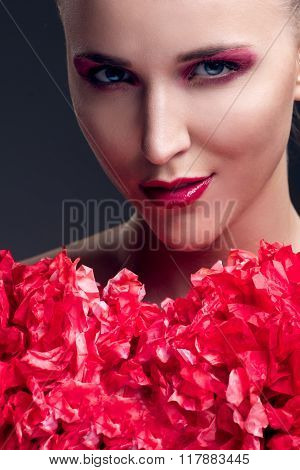 close up portrait of young beautiful woman with red decoration pompon and bright make up