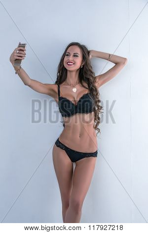 Sexy model in lingerie doing selfie on smartphone