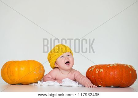Cheerful baby lying beside two large pumpkins