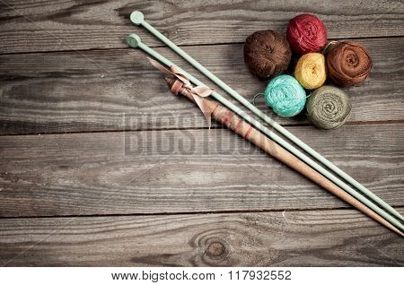 Balls Of Colored Iris Yarn And Wooden Spindle On  Horizontal Boards