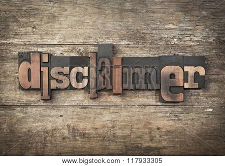 Disclaimer, word written with vintage letterpress printing blocks on rustic wooden background