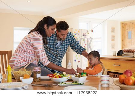 Family In Sitting At Table In Kitchen Eating Meal With Son