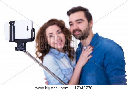 Young Couple Taking Selfie Photo With Smart Phone On Selfie Stick Isolated On White