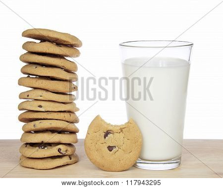 Stack Of 12 Chocolate Chip Cookies Next To A Glass Of Milk
