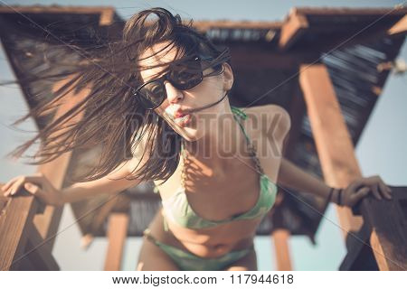 Lifestyle summer portrait,relaxed standing on the lifeguard tower.Happy woman dancing on the beach