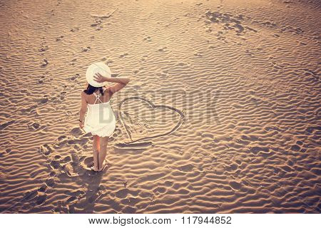 Woman on the beach making heart on the sand.Young woman walking on the sand in a white dress.Relaxed