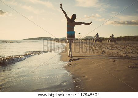 Summer beach woman enjoying summer and sun.Woman saluting quad drivers.Footsteps in sand