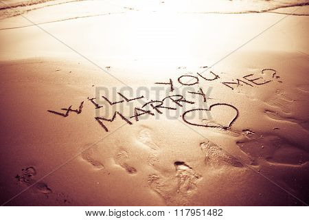 Will you marry me question written on sunset summer sand beach.Proposal on summer vacation.Romantic engagement.Vintage instagram filter