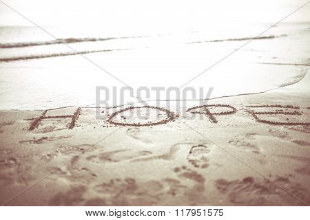 Hope motivational inspiring word written in the sunset sand beach. Concept of hope,optimistic attitude. Expect with confidence. ** Note: Shallow depth of field