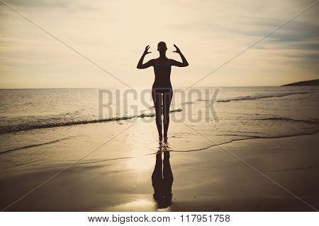 Carefree woman dancing in the sunset on the beach.Vacation vitality healthy living concept.Free woman enjoying freedom feeling happy at beach at sunset.Serene woman in pure happiness and enjoyment poster