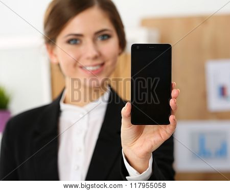 Smiling Businesswoman In Office Hold Cellphone In Hands And Show Screen To Camera
