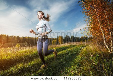 Woman running off road in an autumn forest