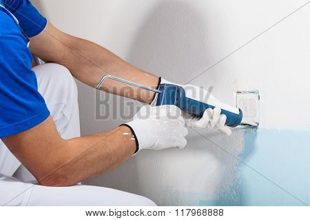 Professional Workman Applying Silicone Sealant With Caulking Gun