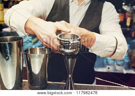 Bartender is squeezing citrus juice in jigger, toned image