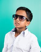 indian kid wearing dark glasses or Goggles, isolated on green, 10 year indian boy in goggles, side profile, closeup poster