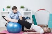 Woman doing physiotherapy exercises with fitness ball poster