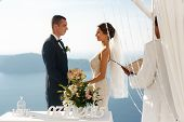 Happy groom and bride at wedding aisle during ceremony with sea in background poster